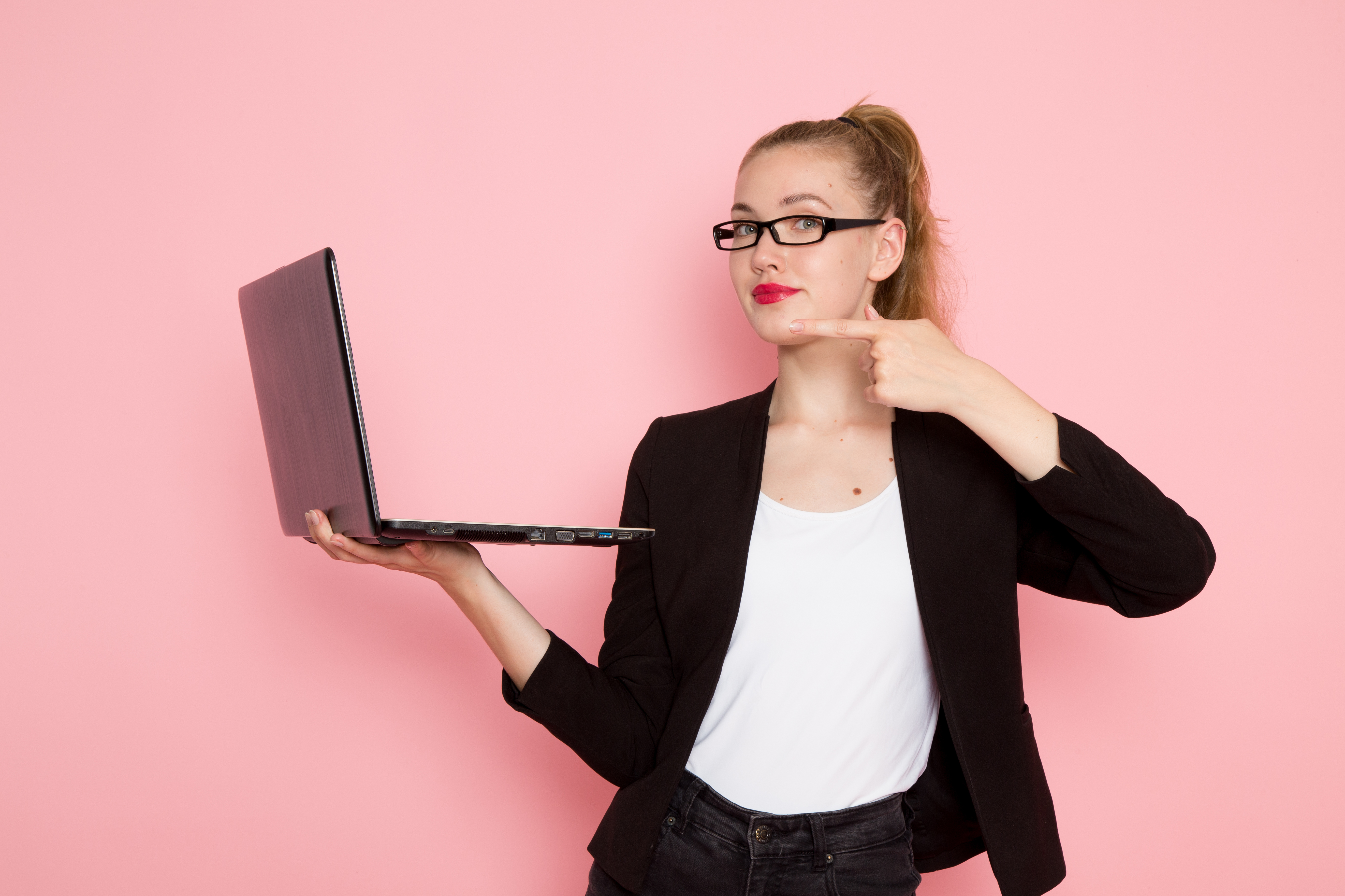 front-view-of-female-office-worker-in-black-strict-jacket-holding-using-laptop-on-light-pink-wall