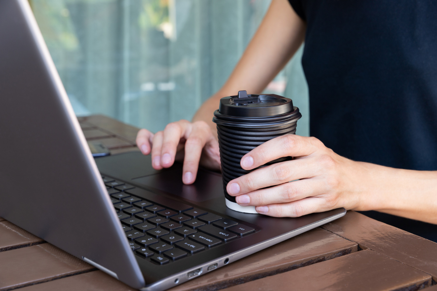 womans-hands-with-paper-cup-of-coffee-or-tea-and-laptop-in-cafe-or-home-terrace