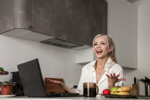 girl-working-on-laptop-in-kitchen-at-home-and-very-emotional-woman-gestures-with-hands